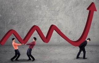 three men holding an upward trending graph