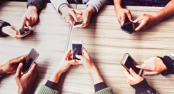 people hands using their mobile phones around a table