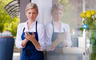 waitress standing outdoors holding a card reader