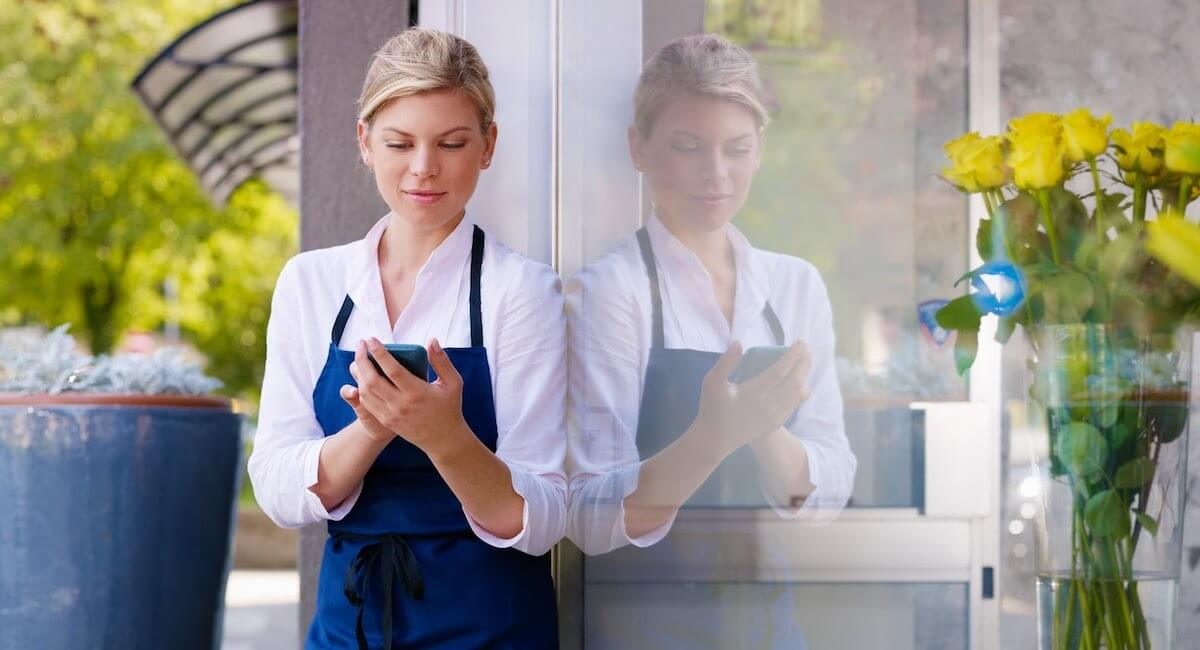 waitress standing outdoors holding a card reader
