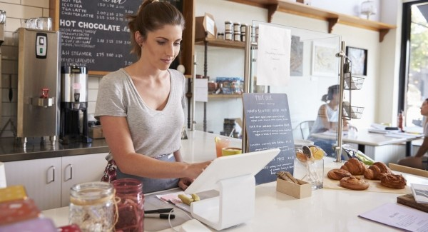 woman using an iPad point of sale system in a cafe