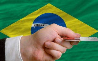 hand with credit card in front of Brazilian flag