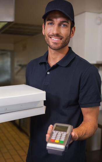 pizza delivery man holding a PDQ terminal