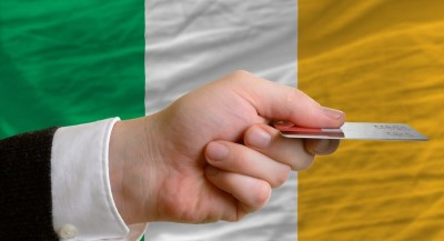 Hand holding credit card in front of Irish flag