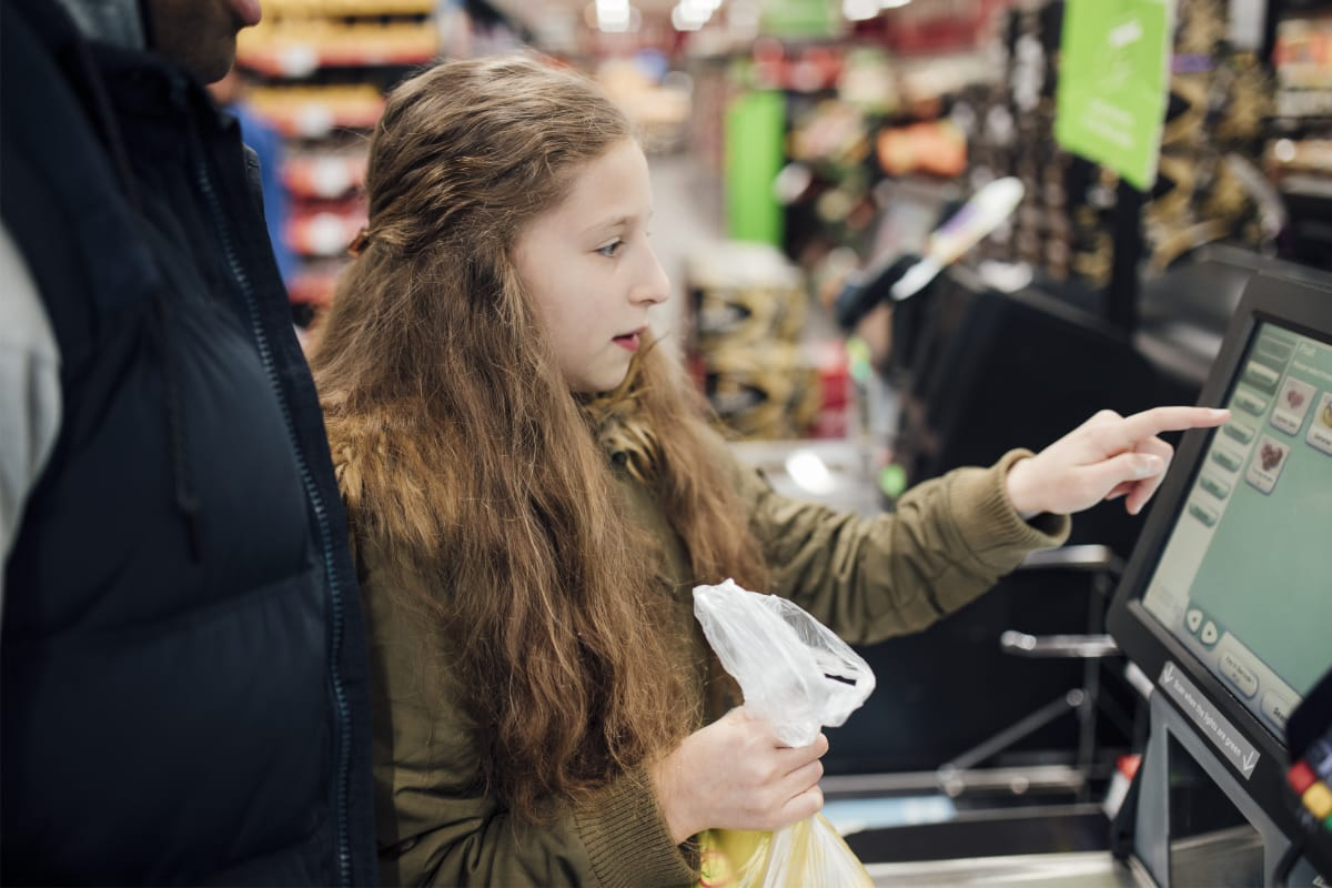 girl at a supermarket self-service checkout
