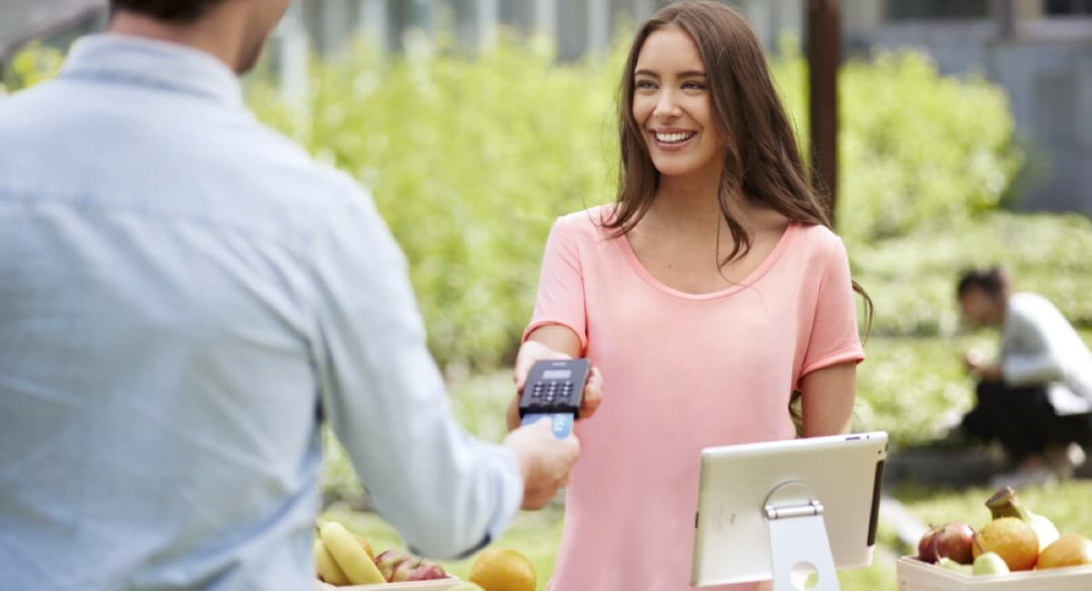 positive woman accepting card reader payment from man