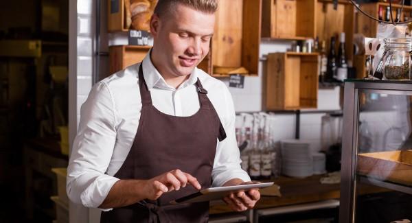 man using iPad POS in cafe