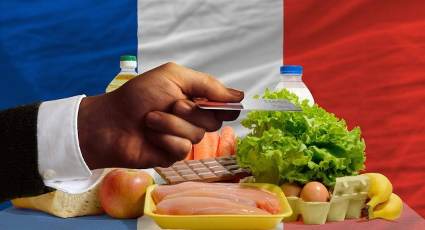 hand holding credit card in front of French flag and selection of food