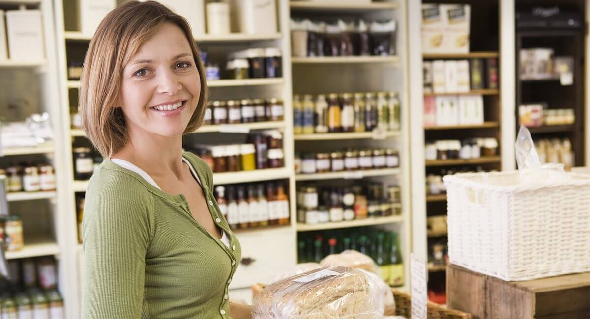 woman with loaf of bread in a delicatessen