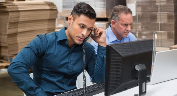 two men using computers and phone in a warehouse