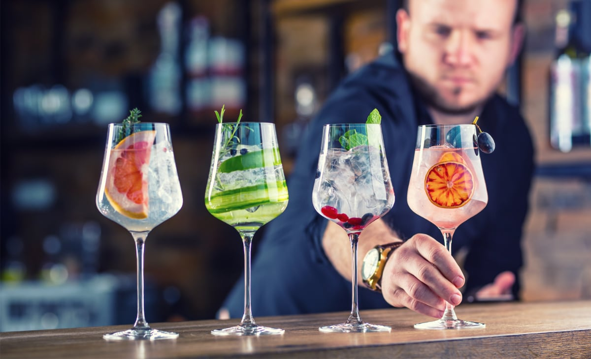 four glasses of cocktails in a bar