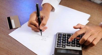 hands calculating acquirer fees for card acceptance