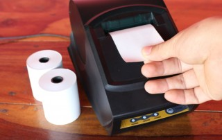 Receipt printer with paper rolls and hand ripping off receipt