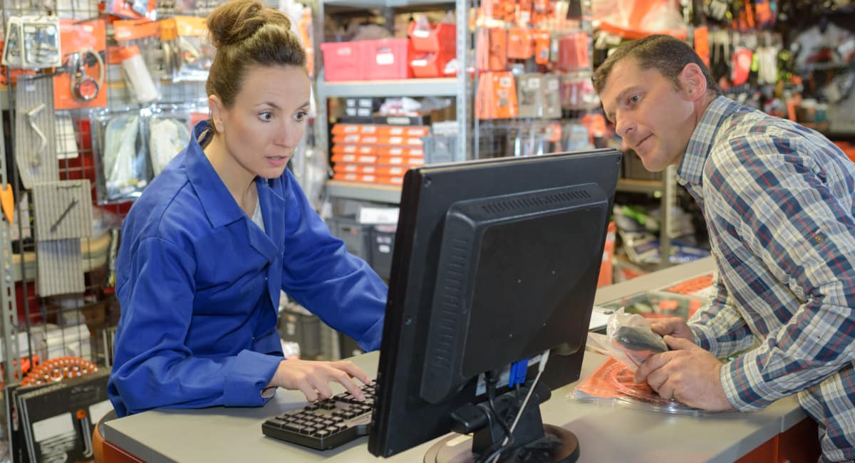 DIY store checkout - shop assistant checking stock levels on computer