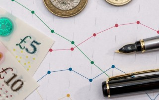 Pound notes and coins with sales figures and pens